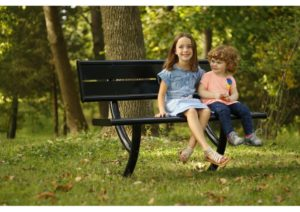A bench set in a park setting with 2 children sitting on top of it