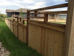 A residential custom privacy wood fence with geometric trim on a sloped backyard
